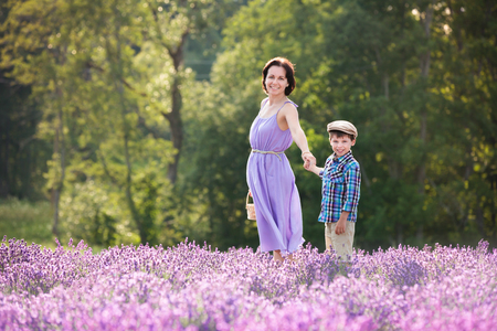 Woman and her little son in lavender field on beautiful summer day Foto de archivo