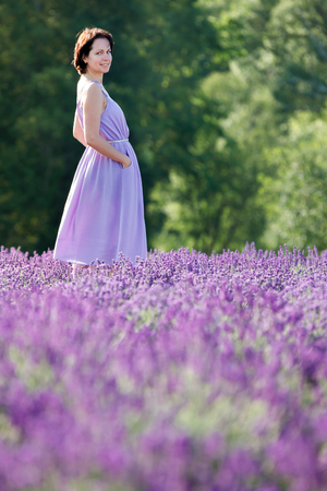Beautiful woman relaxing in lavender field on beautiful summer day