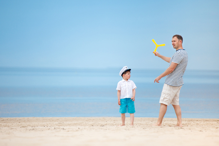 Father and son playing together on the beach  on tropical beach vacation
