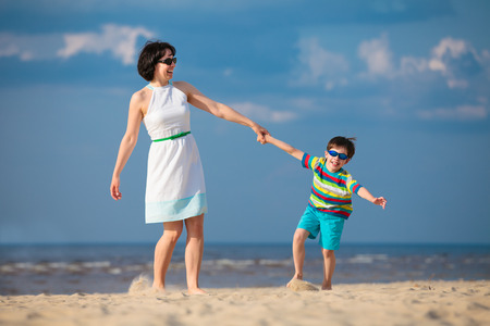 Mother and son having fun during summer beach vacation