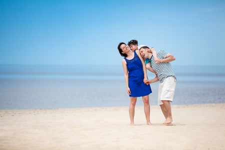 Family of three having fun on tropical beach during summer vacation