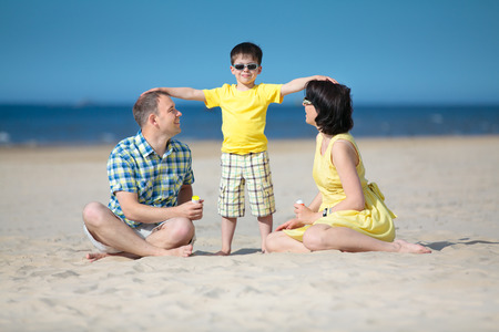 Happy beautiful family of three on tropical beach vacation
