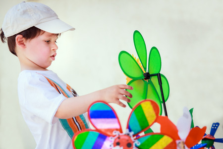Cute little boy with windmill toys on beautiful summer day Foto de archivo
