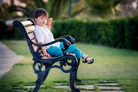 Cute little boy sitting on bench in summer park