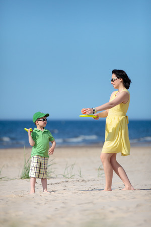 Young mother and son playing on tropical beach