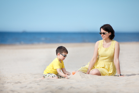 Young mother and her little son playing on sand beach