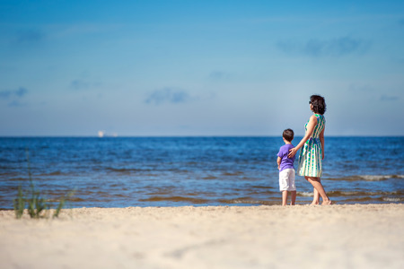 Back view of mother and her cute little son  at summer beach