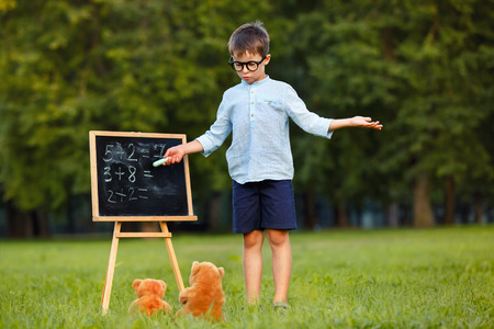 Cute little schoolboy teaching his toys outdoors photo