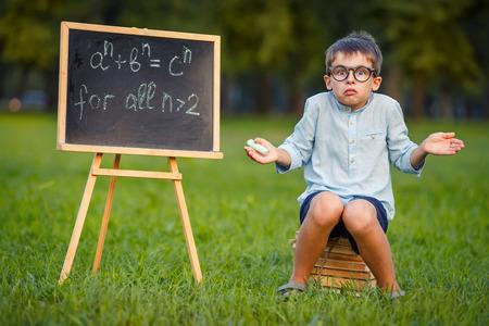 teorema: Cute little estudiante confundido encogi�ndose de hombros no tiene respuesta, pensamiento, desconcertado