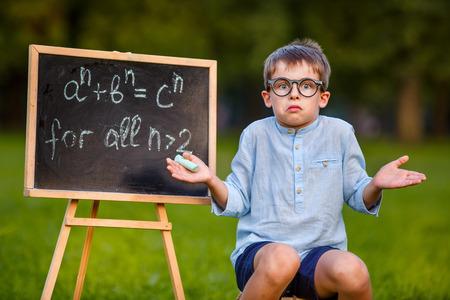 ni�os en la escuela: Cute little estudiante confundido encogi�ndose de hombros no tiene respuesta, pensamiento, desconcertado