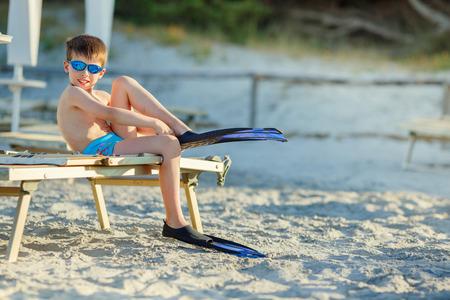 flippers: Niño lindo que pone en el buzo aletas en la playa tropical Foto de archivo