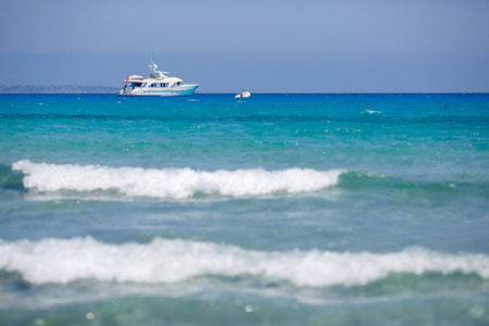 Beach with yacht and kitesurfer in Sardinia on summer day photo