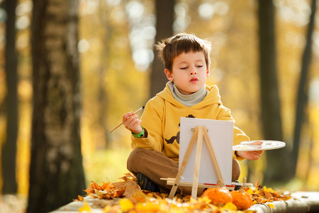 canva: Cute little boy painting in golden autumn park on beautiful autumn day  Stock Photo