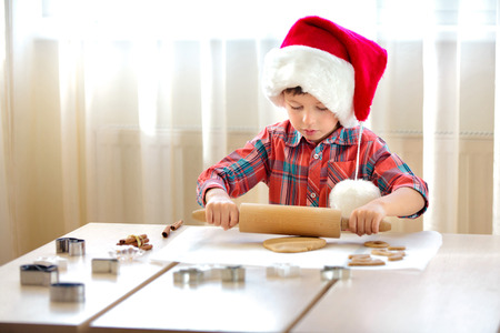 Little boy with rolling pins baking and having fun, Merry Christmas