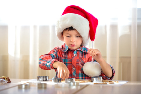 Little boy helping at kitchen with baking cookies, Merry Christmas Foto de archivo