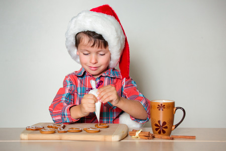 Cute little boy decorating the gingerbread cookies, Merry Christmas Foto de archivo