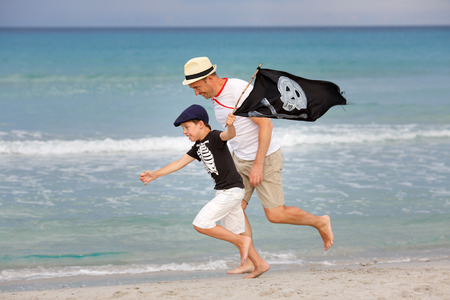 Cute little boy and his father having fun on tropical beach