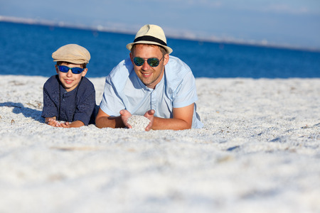 Happy father and his son having fun at quartz pebble beach, Sardinia, Italy