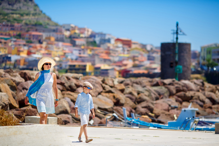 Mother and her little son walking outdoors in town Castelsardo, Sardinia, Italy Foto de archivo