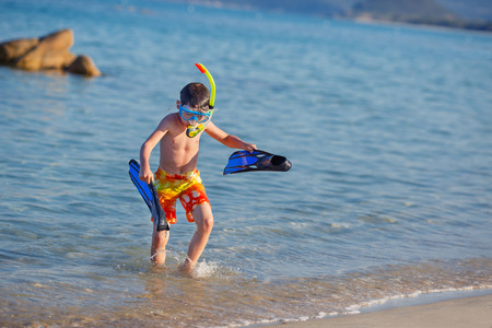 Vacation boy happy snorkeling running having fun in water splashing holding fins during summer holiday vacation