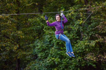 Young woman having fun on long rope route in adventure park