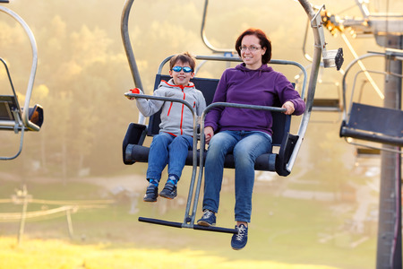 Happy mother and her little son ride chair lift in Sigulda, Latvia, Europe Foto de archivo
