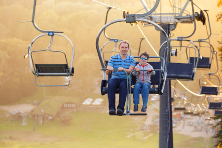 Happy father and her little son ride chair lift in Sigulda, Latvia, Europe Foto de archivo