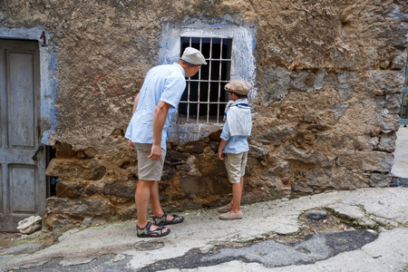 Father and his little son walking in village Orgosolo, Sardinia, Italy Foto de archivo