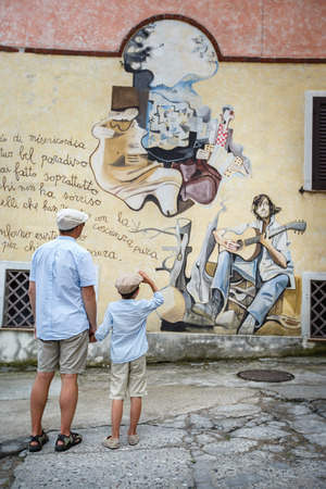 Happy father and son walking outdoors in village ORGOSOLO, ITALY. Murals wall paintings about political and historical facts in Orgosolo, Sardinia, Italy