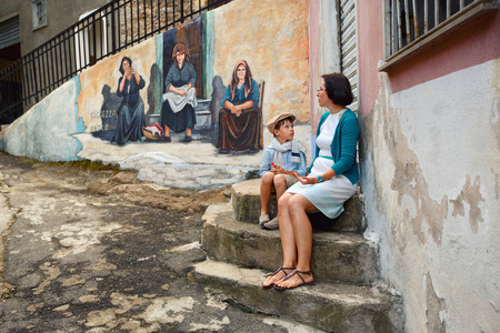 murals: Young mother and son walking outdoors in village ORGOSOLO, ITALY. Murals wall paintings about political and historical facts in Orgosolo, Sardinia, Italy Editorial