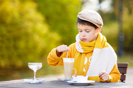 Cute little boy drinking hot chocolate in cafe on beautiful autumn day