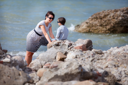 Young loving mother talking with her little son on a rocky seashore