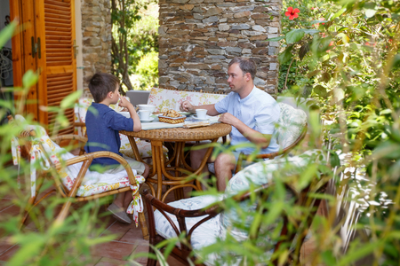 Father and son having breakfast together outdoors