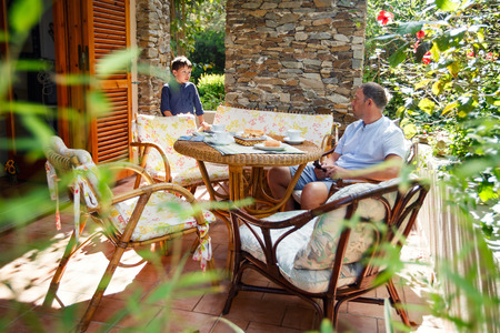 one family: Father and son together on patio on beautiful summer day Stock Photo