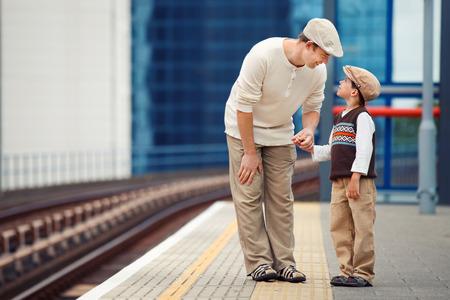 padres hablando con hijos: Joven padre e hijo esperando el tren en la plataforma de la estaci�n de tren Foto de archivo