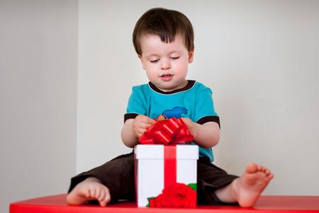 Happy toddler boy opening gift box indoors photo