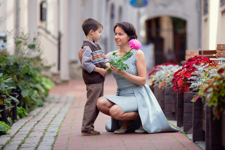 giving: Little boy giving flower to his mom outdoors Stock Photo