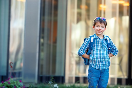cute young boy: Portrait of cute school boy with backpack outdoors