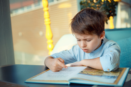 kid reading: Boring and tired little boy reading book for elementary school