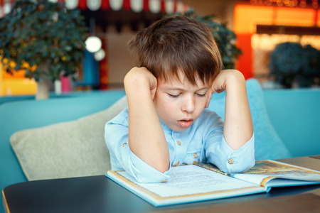 troubles: Boring and tired little boy reading book for elementary school