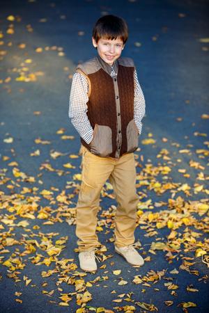 boy beautiful: Admiring little boy laughing outdoors at beautiful autumn park