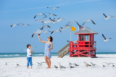 Young mother and her little son feeding seagulls on tropical beach, Florida summer holiday vacation