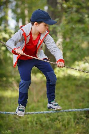 climbing: Little boy enjoying activity in the park. Cute little child having fun outdoors climbing on playground