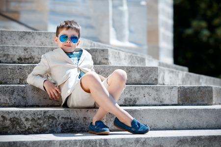 Kleiner Junge, der in einem schönen Anzug und Gläser. Zurück zur Schule. Kinder Porträt. Stilvolle Kind im Anzug