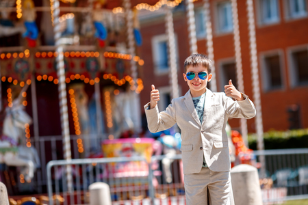 beautiful little boys: Stylish kid in a nice suit and glasses near the traditional French merry-go-round showing thumbs up, Beauvais, France Stock Photo