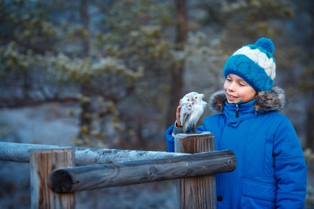 animal health: Cute little boy with owl toy on shoulder in winter forest
