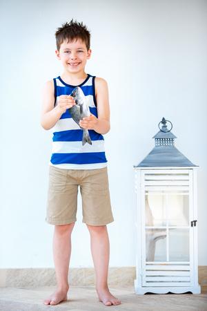 gilthead bream: Cute little boy holding a gilt-head sea bream