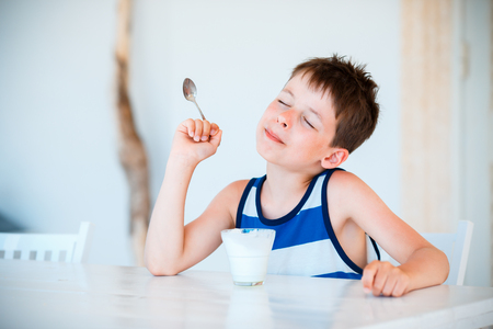 Portrait of smiling little boy eating delicious yogurt