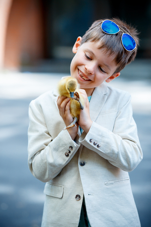 handsome boy: Cute little boy holding his pet baby goose outdoors