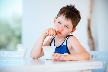 child ice cream: Portrait of smiling little boy refuses to eat delicious yogurt
